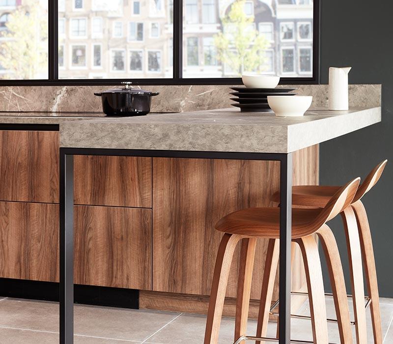 Bruine keuken met bar en zwarte greeplijsten