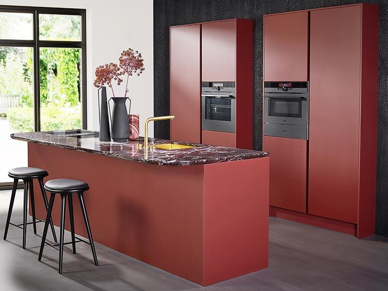 Rode eilandkeuken met hoge keukenkasten